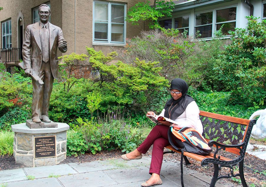 Student sits studying on campus bench beside Walter R. Garrison statue.
